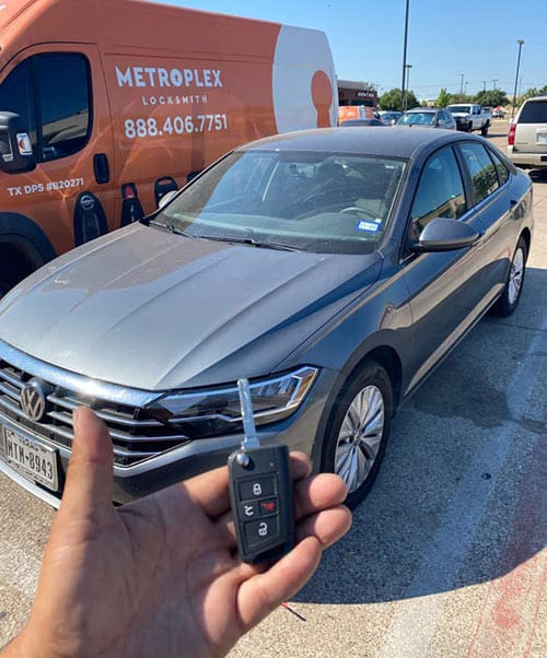 image of one of our locksmith vans behind a VW in a parking lot with our technician holding up the new flip key they cut and programmed on-site.